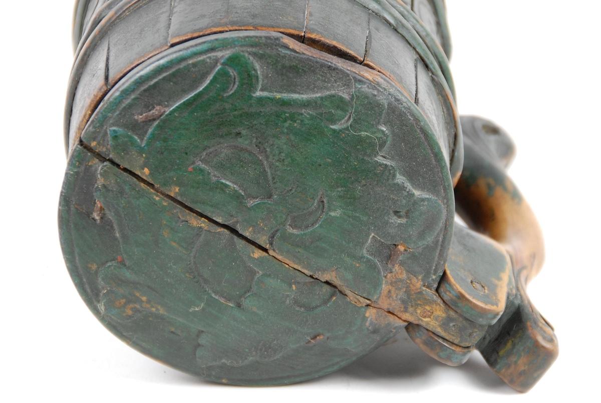 Kanne av furustaver. Relieffskåret akantusranke. Bladorm på lokk og hanke. Grønnmalt.