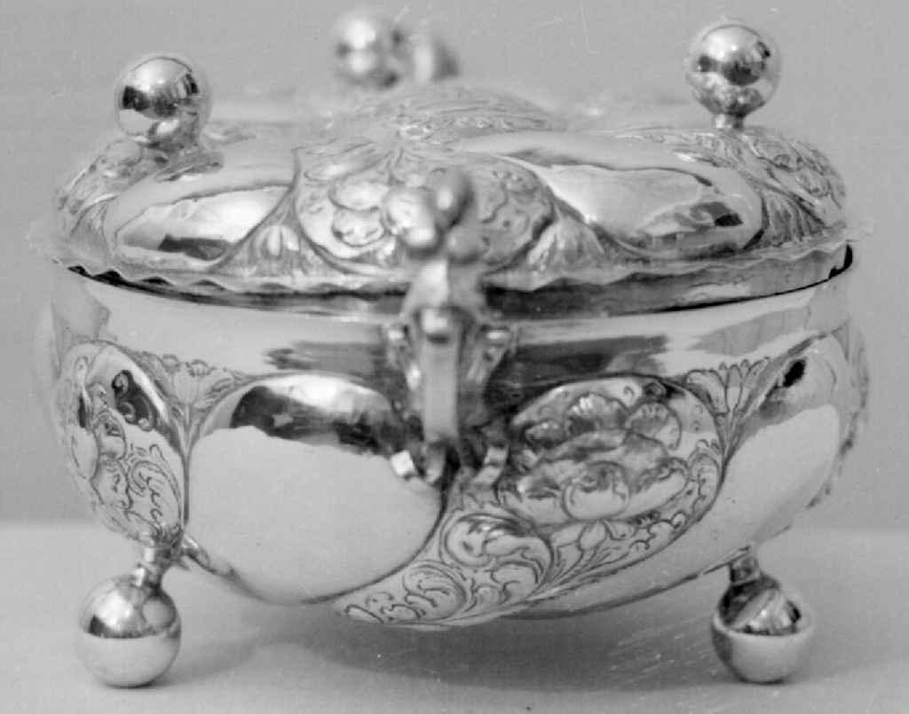 Terrin av sølv, med lokk. Terrinen er avlang rund og har barokkdekorerte håndtak på kortsidene. Terrinen har gravert og siselert barokkdekor på korpus og lokk, av blomster og akantusranker. Står på fire runde føtter.