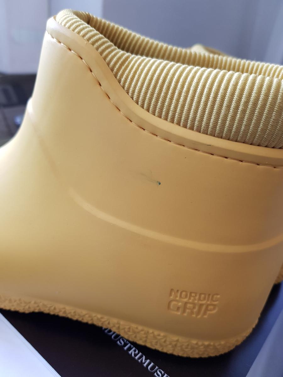 Ankelhøye gummistøvler med micro-fleece fôr, Thermo-liner, løs innersåle, ribbet og polstret tekstil langs åpningen, liten stropp øverst midt bak og  stjernemønstret kant ned mot sålen. Overdelen støpt av to halvdeler, med synlig støpekant midt foran og ned midt bak på hælen.  Sålen har dypt mønster i form av likesidede trekanter, hvorav 3 på helen og 7 foran på sålen, har stor friksjon.  Sålen har såkalt IceLock technology, utviklet av Hypergrip, som gjør dem glisikre innendørs, samtidig som Micro-glass filamenter i sålen gir godt grep og friksjon på is og vått føre utendørs. NB! Ved utpakking av støvlene for bortlegging på magasin, etter to utstillingsperioder, oppdages et lite kulepennmerke på yttersiden av venstre støvelskaft. Materialkonservator Peter Juga har fjernet dette ved hjelp av Etanol.
