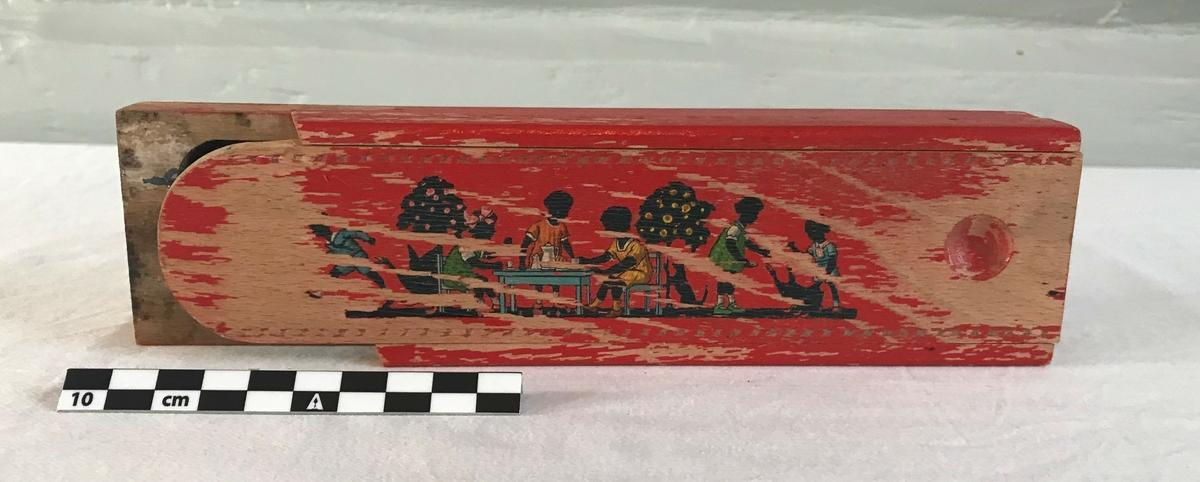 På lokket er det avbildet seks barn som leker: Fra høyre til venstre, en gutt som løper, tre barn som leker teselskap, samt to barn som leker med en hund.