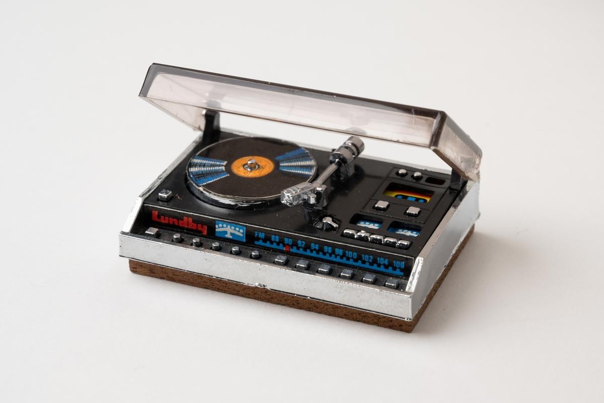 Grammofon till dockskåp. Skivspelare i svart och silverfärgad plast med brun träsockel. Locket i rökfärgad plast är öppningsbart. Kassettbandspelare och radio ingår i apparaten.