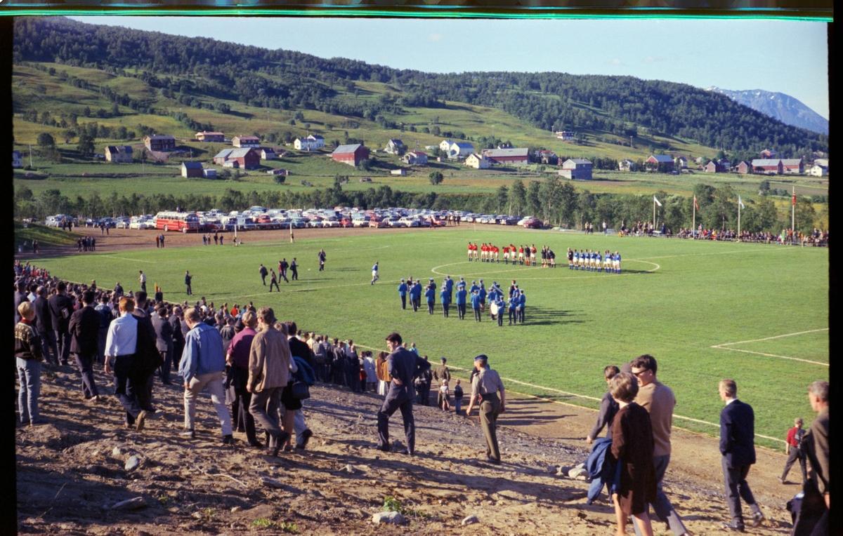 To fotballag og et musikkorps på Blåbærhaugen stadion. Publikum i forgrunnen.