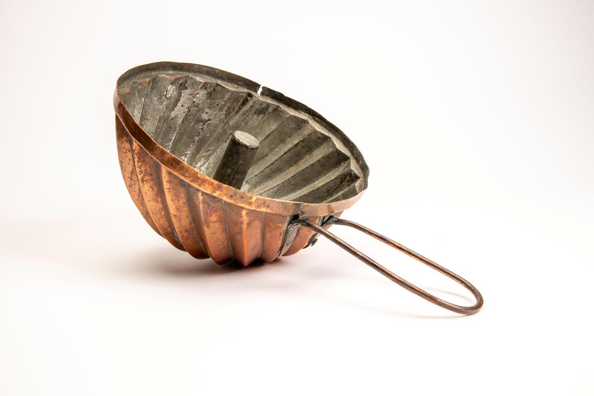 Dyp puddingform med brede riflede sider, rifler på skrå, dypt hull midt under, på innsiden oppstående tapp. Hank av en bøyd kobberstang. Flatt lokk med oppstående karm, tverriflet kant rundt hanken.