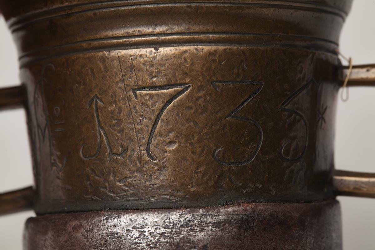 Morter og støter av messing. Morteren har en jerngjurd nederst, antakelig som en forsterkning. Firkantede hanker på sidene. Støteren har en profil midt på skaftet.