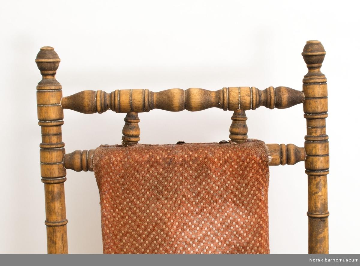 Barnegyngestol, amerikansk, i bøk og bjørk med spor etter svart maling. Svartmalte stoler av denne typen var vanlig. Malingen er trolig fjernet. Finnes også rester av hvitmaling. Kan være malt hvit før malingen ble fjernet. Rygg- og setetrekk er trolig trukket på ny. Understellet er festet til meiene med fjører.