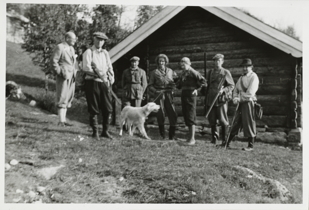 Vertinne og gjester, hvorav to med jaktvåpen. utenfor hytten til Lizzie Michelet, antagelig før eller etter jakt. Hovden i Telemark.