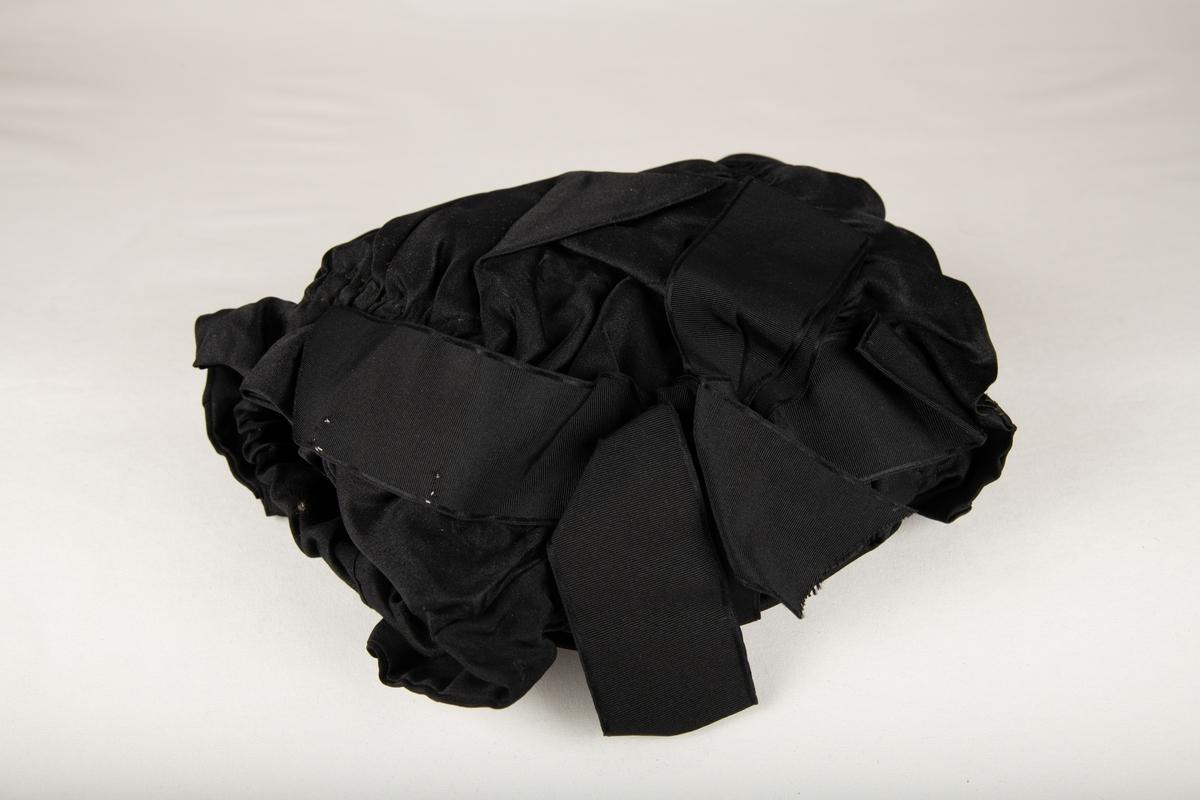 Forholdsvis liten muffe med forsiden sterkt rynket, en  rynkekappe  langs åpningene. Nederst en sort sløyfe i silkerips. Foret har sort strikk rundt åpningene.
