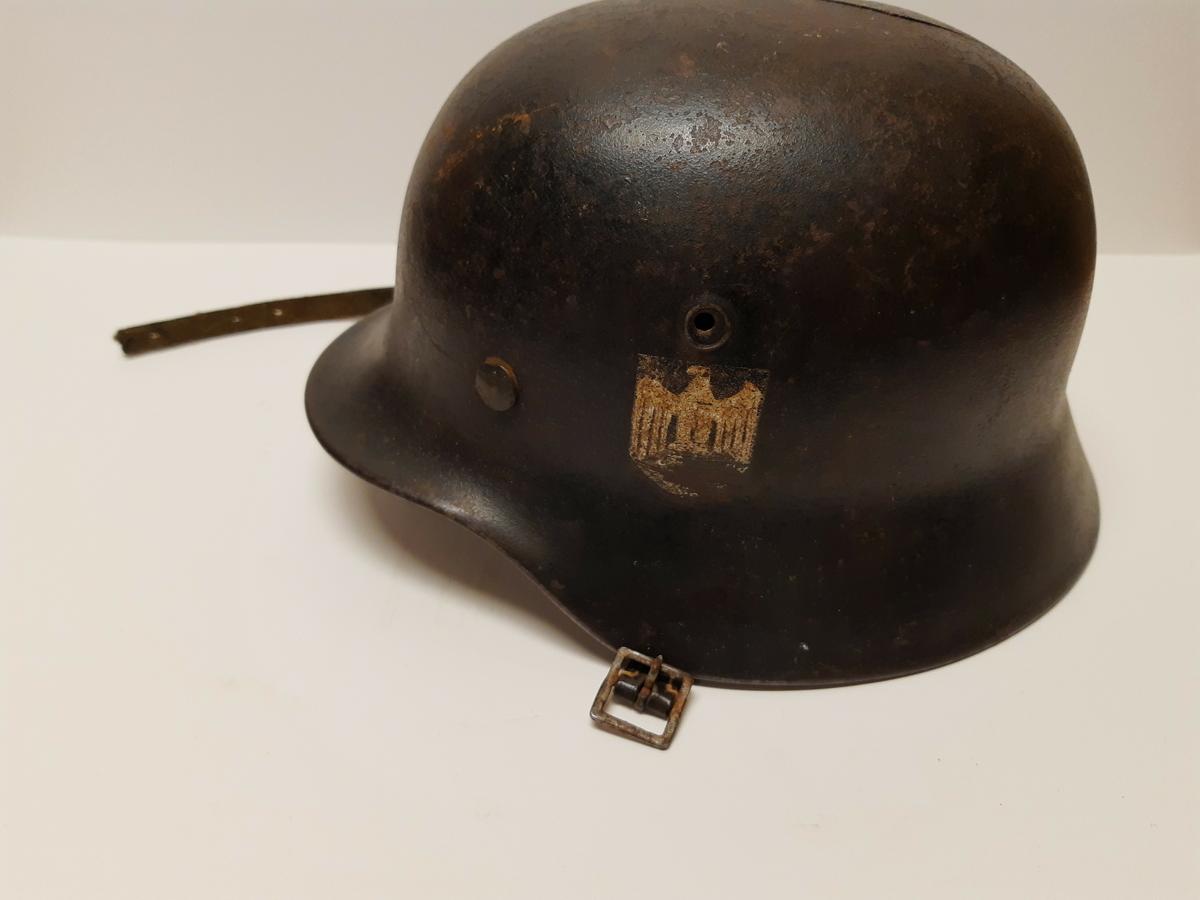 Stålhjelm av typen brukt av tyske soldater under 2. verdenskrig. Hjelmen har rem med spenne til å feste under haken. På venstre side er hjelmen dekorert med riksvåpenet til det tredje riket, ørnen over et hakekors. Merket er veldig slitt.