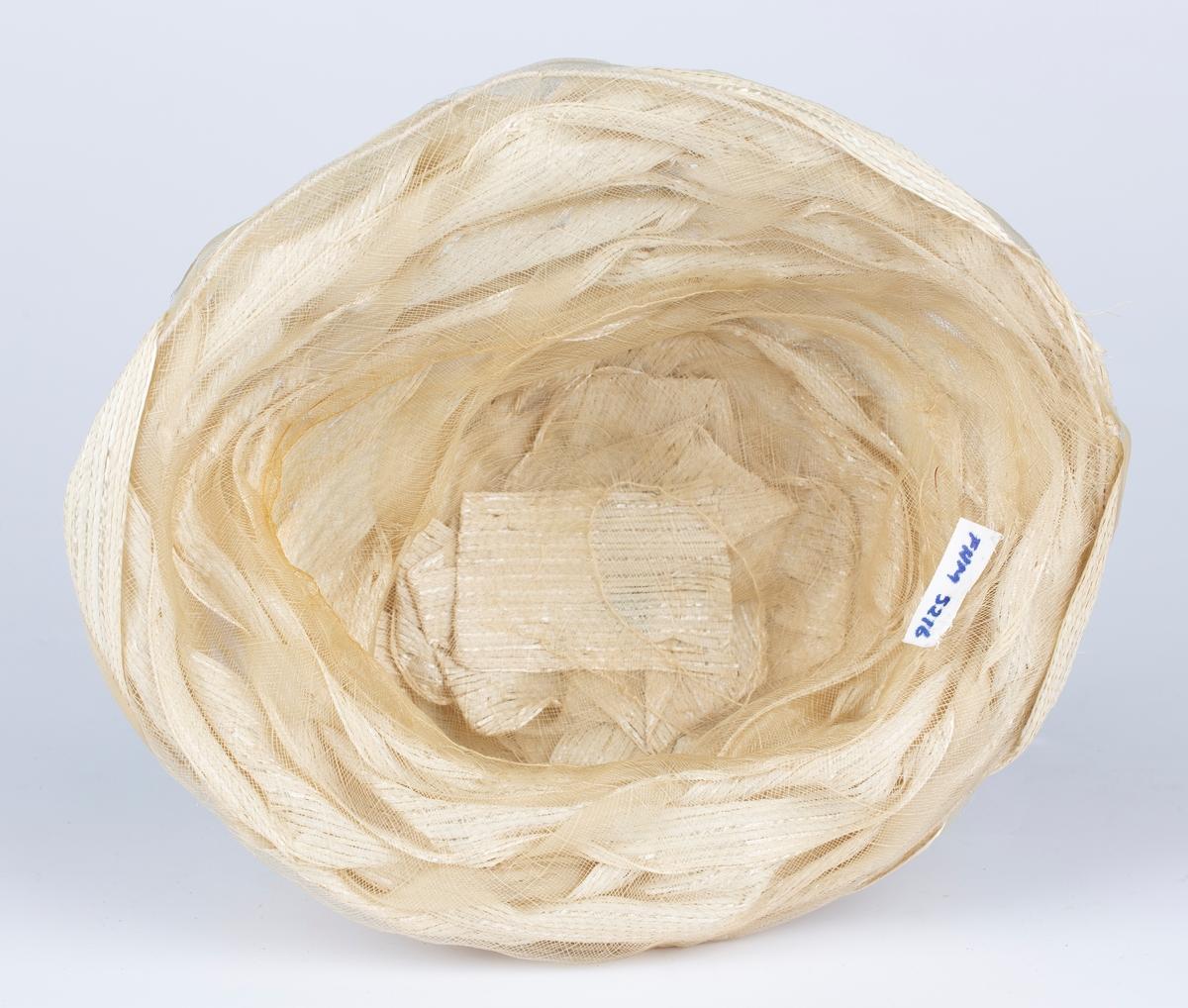 Damehatt i slørliknende plastmaterialer, vevet plast og plastnetting flettet i hverandre.