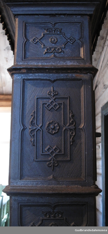 Etasjeovn med tre etasjer. Stiltrekk fra historismen på slutten av 1800-tallet. Brennkammeret har avskårne hjørner, er smalt, rektangulært med ilegging fra kortenden, enkel kokeplate med ringer på toppen samt askebakke foran døren. Står på fire bein av støpejern, bukkeføtter med bruskformer. Etasjekamrene har små dører med smijernsdekor.