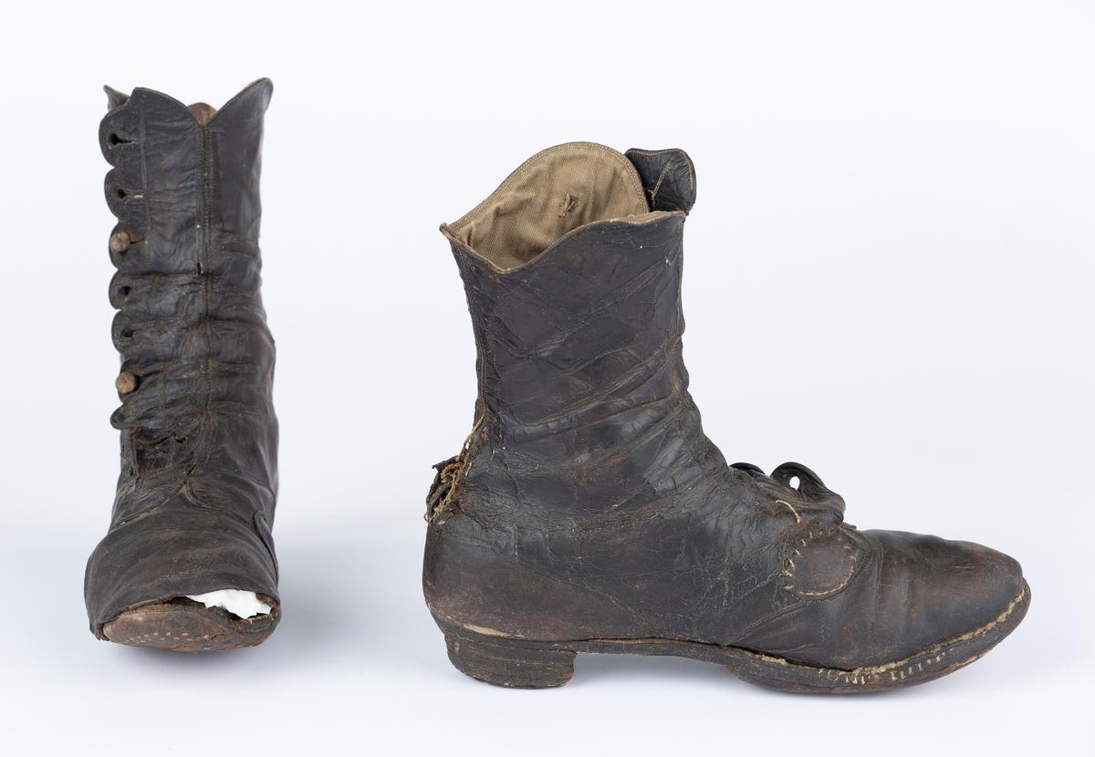 Halvhøye knappestøvler, 9 knappehemper, lær foret med lerret. utslitte, reparert og bøtt flere steder.