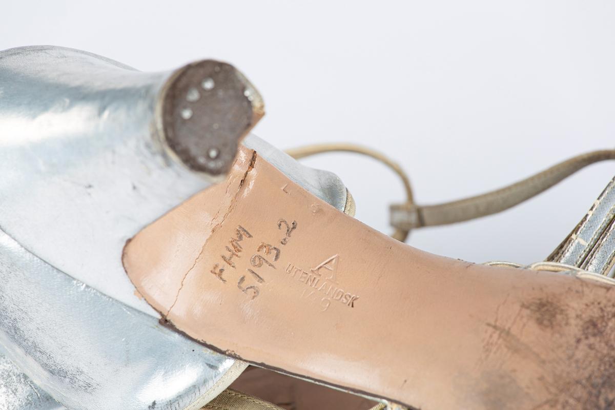 """Damesko, ett par. Høy hæl, tett hælkappe. Flettet med tett tåspiss. Regulerbar T-rem overvristen. Foret med skinn foran og med tekstil i hælen. På utstilling i 1993: """"Kjolekø og Knipling - miniskjørt og thigts. 1993. Sølvfarget"""