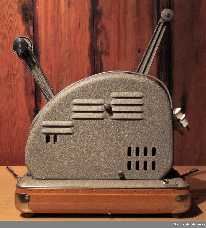 Smalfilmapparat montert på bunn med fire klemmelåser for påsetting av beskyttelseslokk. Lokk av laminert plastmateriale. Inne i lokket er det montert en liten høyttaler samt en høttalerkabel på rull.