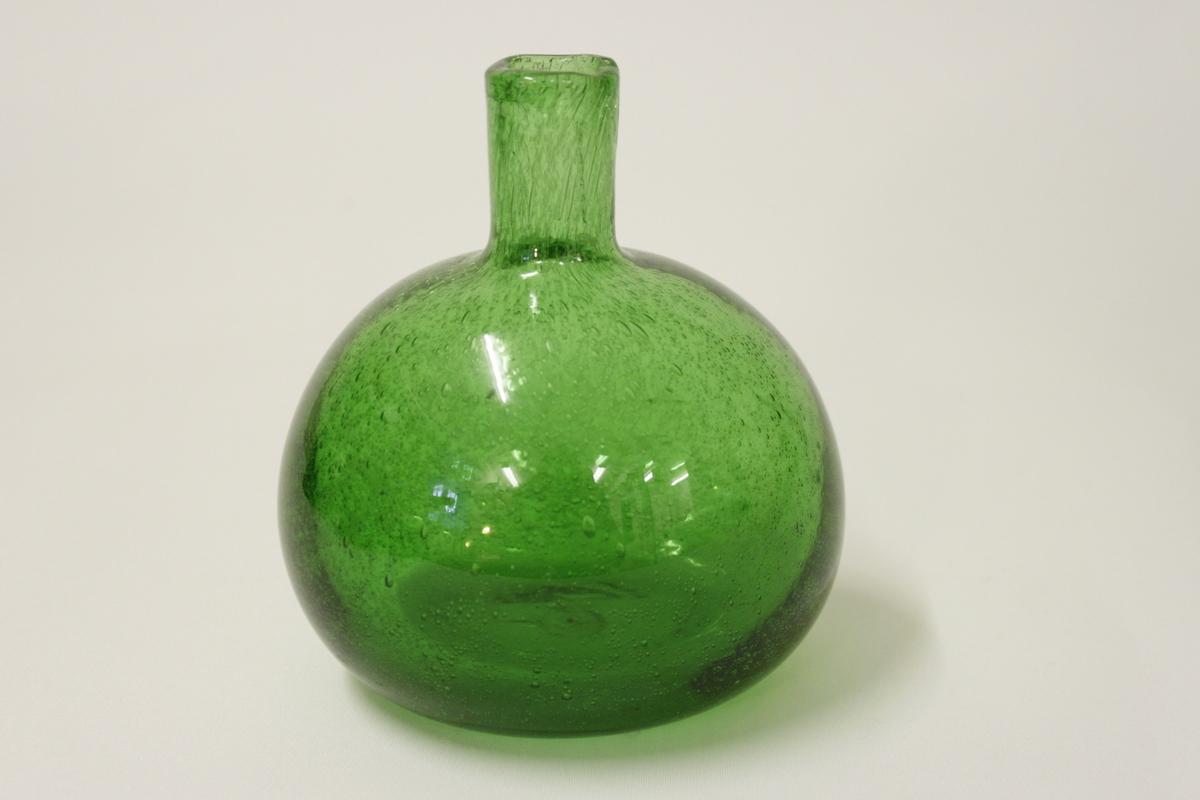 Glasflaska använt i bikupa för socker och vatten. Bullig grön glasflaska med ena sidan slät.