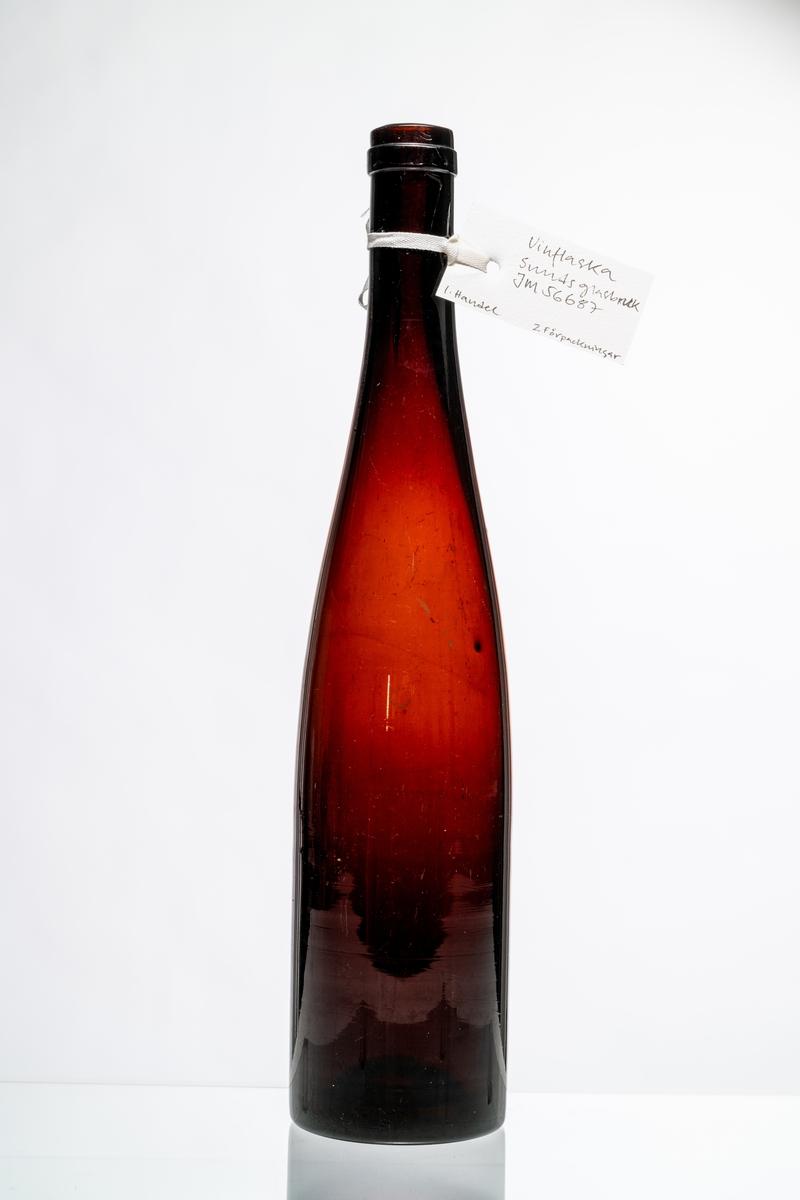 Vinflaska, fransk modell, av röd-brunt glas, avsedd för tillslutning med naturkork. Flaskan tillverkades även i grön färg. Hantverksmässigt tillverkad vid Sunds glasbruk, Jönköpings län. Se vidare Historik.
