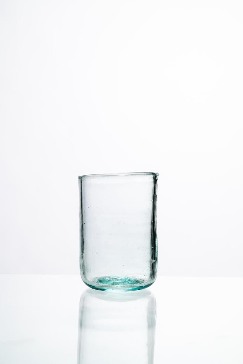 Dricksglas av klart, något grönfärgat glas. Rak modell, ojämn höjd, plan botten med puntelmärke. Hantverksmässigt tillverkat på Sunds glasbruk, Jönköpings län. Se vidare Historik.