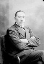 Porträtt av en man med mustasch som sitter i en fåtölj med a