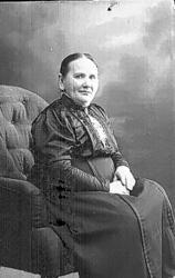 Porträtt av en kvinna som sitter i en fåtölj med händerna i