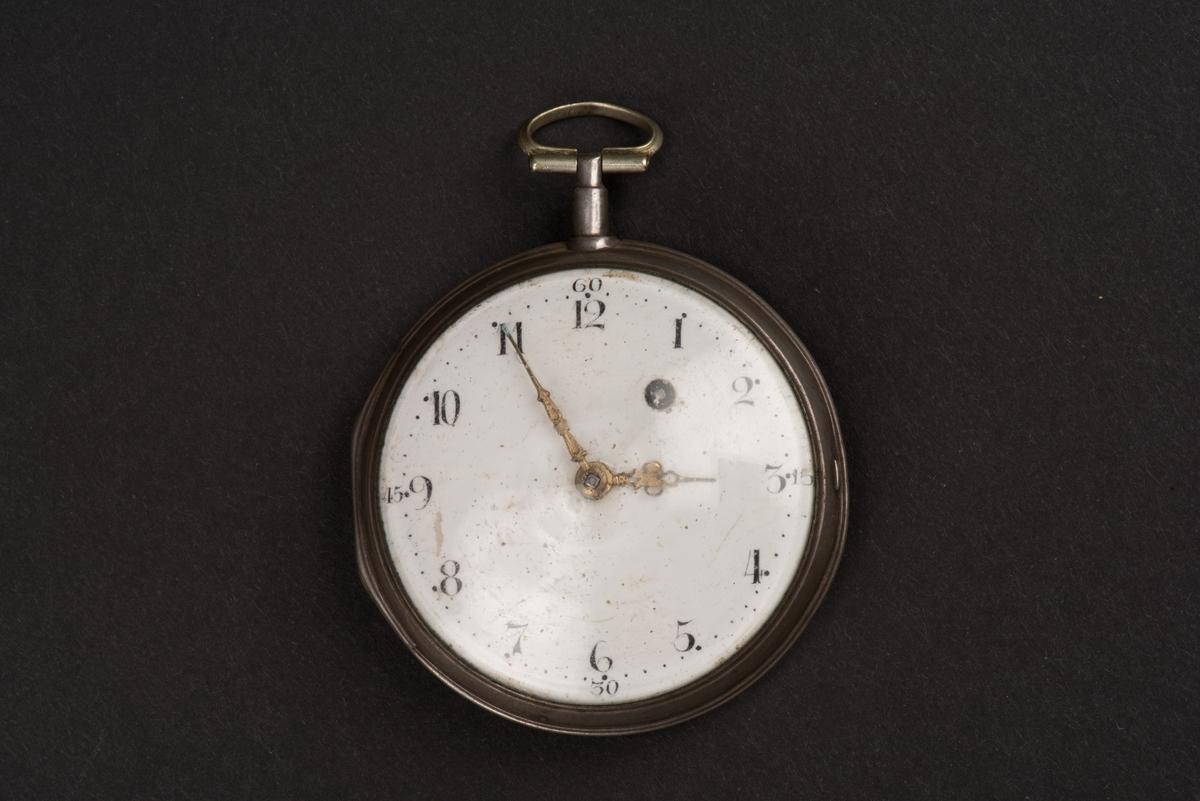 Runt fickur med spindelverk. Boetten är tillverkad av silver och locket av glas. Ett fäste sitter överst för klockkedjan. Urtavlan är av vit emalj och har arabiska siffror samt markeringar för minuter i svart. Tim- och minutvisarna är förgyllda. Uppdraget är placerat vid 1:an.  Spindelverket är graverat och visar att det är tillverkat av Peter Svanberg i Linköping.  Boetten är stämplad av Olof Strömwall i Norrköping år 1795.