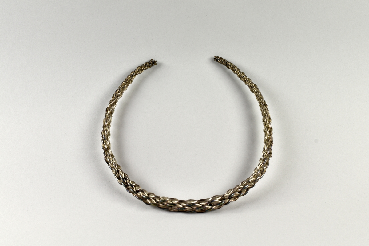Öppen, stel, halsring av silver från vikingatid. Tillverkad av åtta tjockare silvertrådar som är sammanflätade. Halsringen är tjockare på mitten och smalnar av mot ändarna.