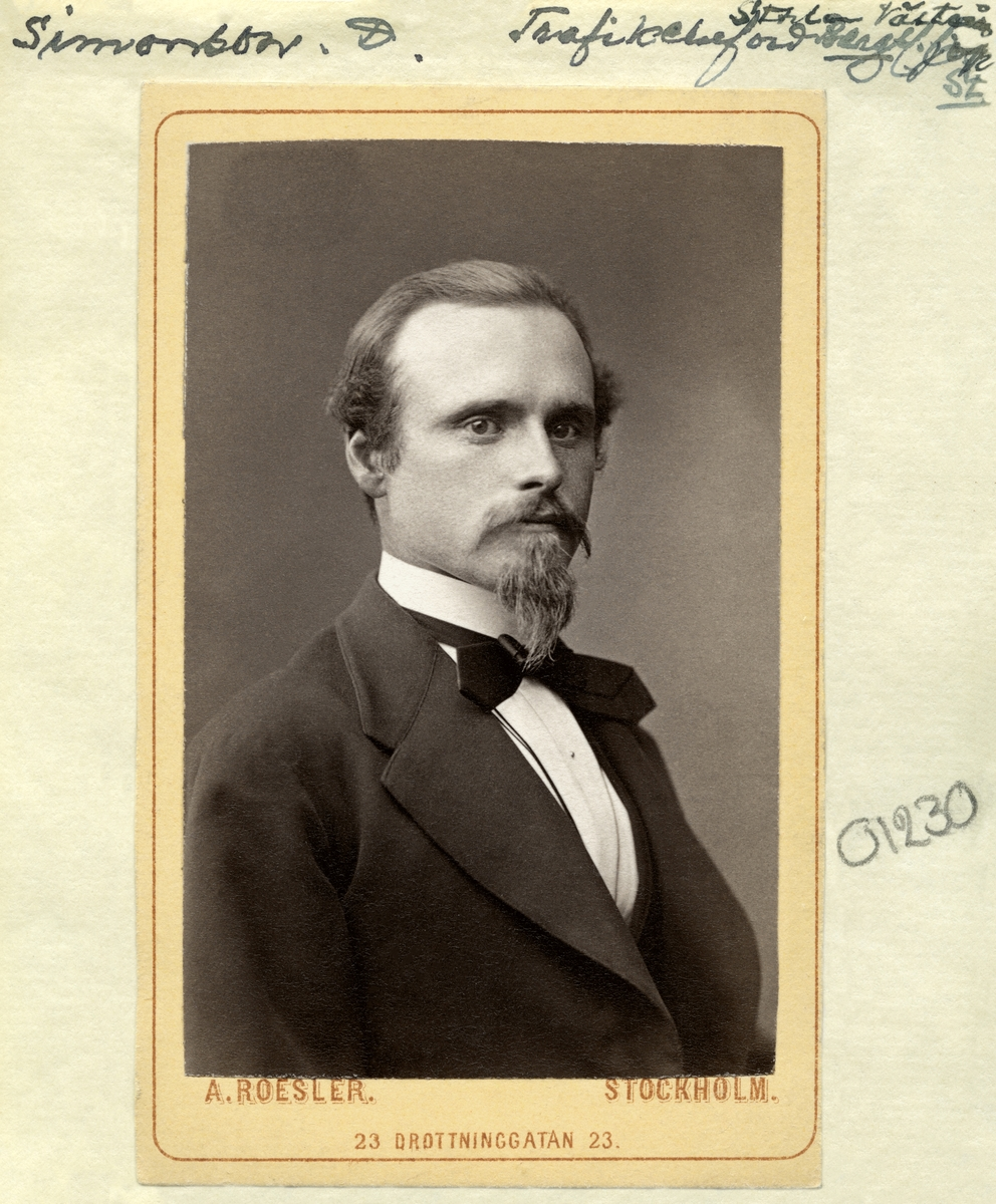 Porträtt av trafikdirektör Jonas Didrik Simonsson. Född 1849 i Bankestad, Hägerstad socken som son till Simon Simonsson och Johanna Lovisa Jonsdotter. I vuxen ålder inledde han sin karriär som stationsskrivare vid järnvägsstationen i Norrköping. År 1875 gifte han sig med den närmare 20 år äldre Brita Cecilia Harlingzon och paret bosatte sig vid Östra Deje järnvägsstation i Värmland där Simonsson fått tjänst som stationsinspektör. År 1881 flyttade paret till Göteborg där Simonsson efterhand lät sig uppgraderas till trafikdirektör vid Bergslagernas station. Karriären förde honom vidare till Stockholm där han som verkställande direktör blev änkling 1914. Ny livskamrat fann han i sångpedagogen Anna Katarina Bergström. Paret gifte sig 1916 och var i förstone bosatta på Lidingö för att senare flytta till en våning på adressen Strandvägen 35. Han avled i sitt hem den 27 mars 1923.