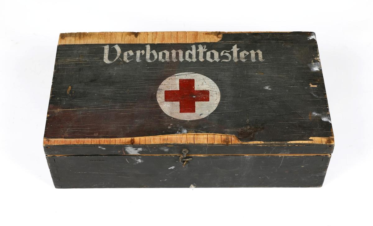 Tyskprodusert treskrin til sanitetsutstyr brukt i felt under andre verdenskrig. Skrinet kan lukkes med en metallhempe. På lokket er det skrevet Verbandtasten og malt på et rødt kors i en hvit sirkel. På innsiden er det ro rom og på lokket er det festet en papirlapp hvor det er skrevet: Inhaltsverzeichnis des Kfz. -Kastens 1 Flasche Jodtinktur 5 Sicherheitsnadeln 4 kleine Verbandpekehen 6 grosse Verbandpekehen 1 Dreiecktuch 1 Abschntirbinde 2 Brandbinden 1 Presstück 1 Packet Polsterwatte 1 Drahtschiene 1 Rolle Leukoplast 1 Raiserklinge als Ersats für Kleiderschere