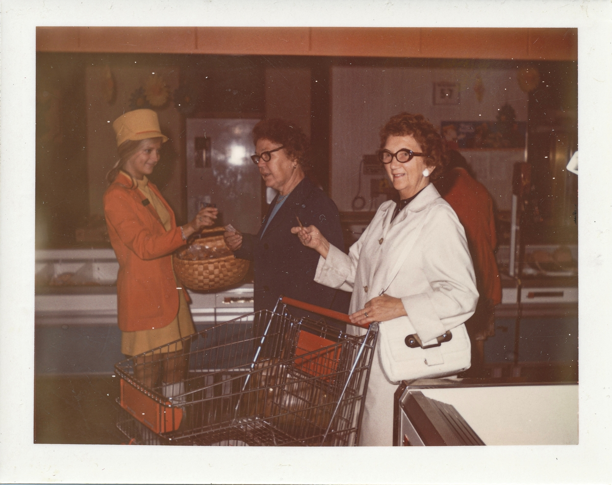 Mataffärssinteriör med kvinna som delar ut smakprover till två kunder.