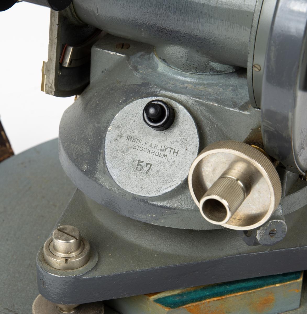 Kikarinstrument monterat på platta. Instrumentet har belysningsknapp för belysning i ockular. Instrumentet har en huva/hölje av grå metall. Över huven går en rem i skinn som knäpps med spänne fastsatta i bottenplattan. Skinnremen över huven är inte original, skinnbitarna i spännet är original.