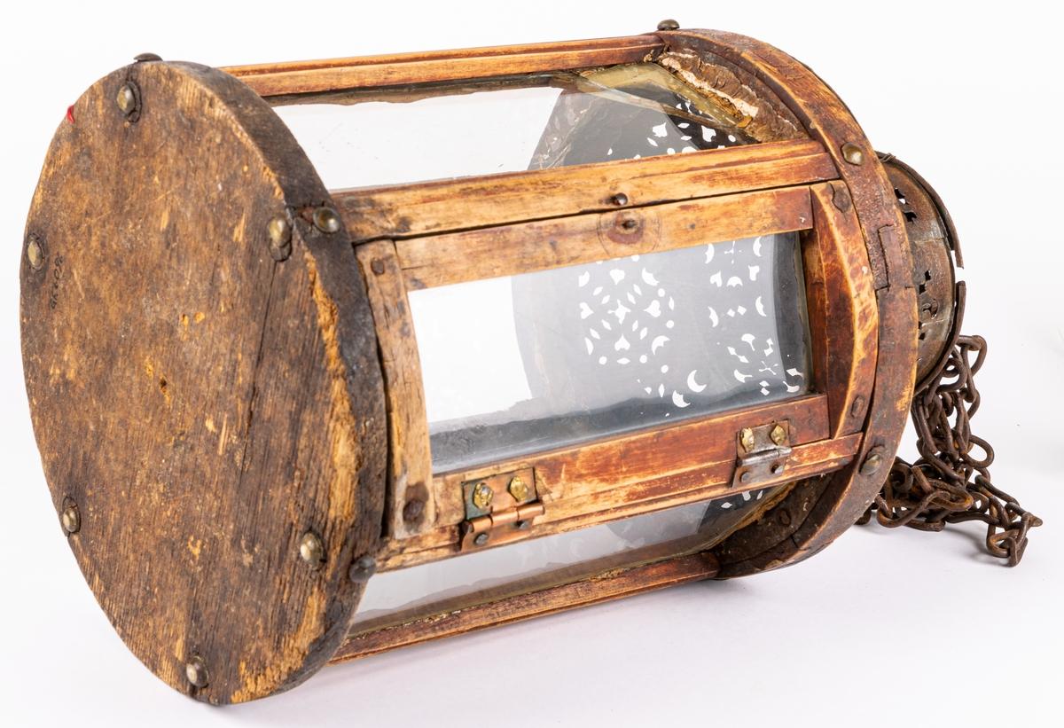 Handlykta, rund, med träbotten på vilken står kort och vid ljushållare, Sidorna glasväggar infattade i lodräta trästavar. En sidan kan öppnas som dörr. Sex-sidig. Överdelen av järn, lutande tak med cylindrisk överdel. Genombrutet mönster. Handtag och kedja av länkar.
