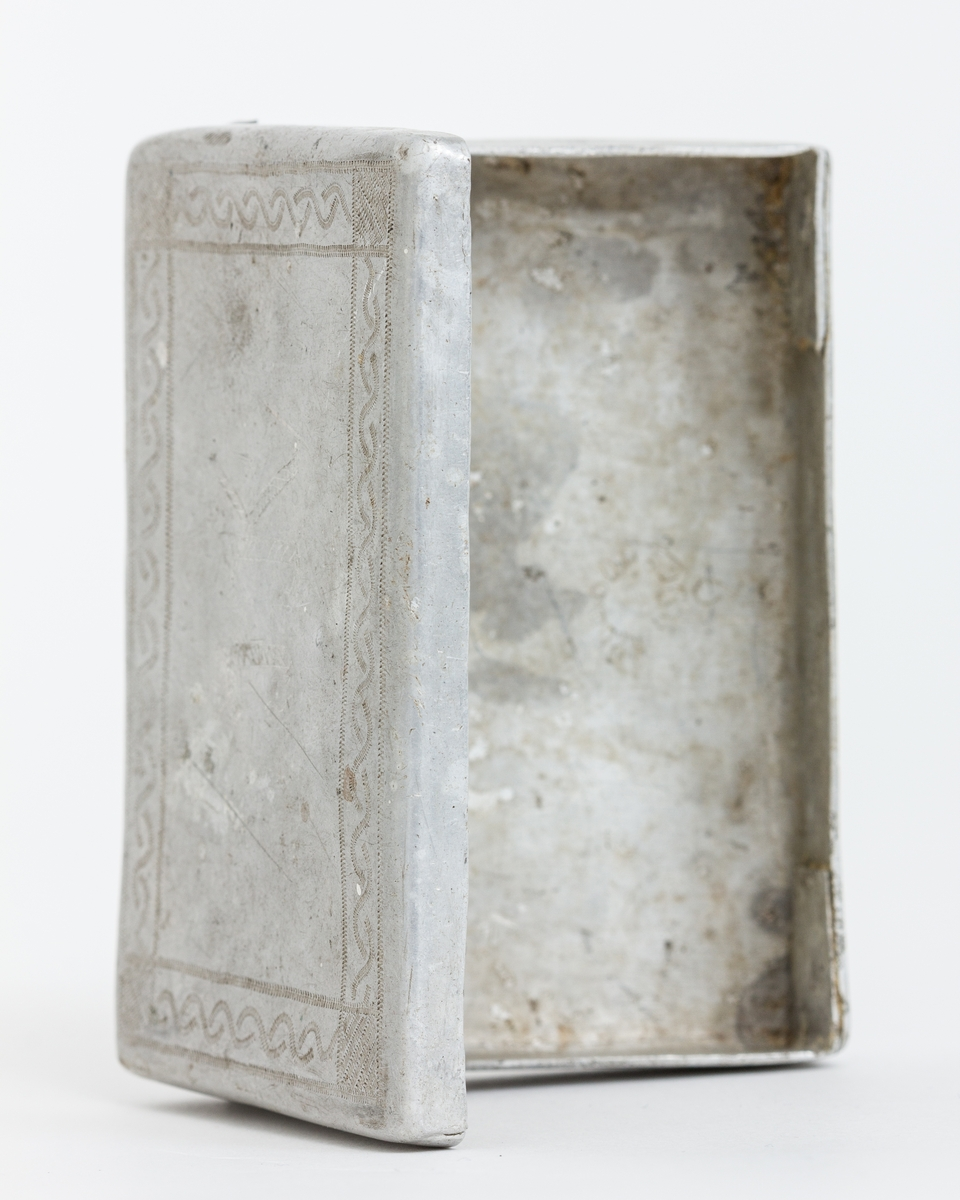 Sigarettetui lagert av sovjetiske krigsfange. Framstil av aluminium og lokket er dekorert med stempelpregede border og initialene I (J?)K. Lokket er klinket fast med en liten bolt i hver kortende.