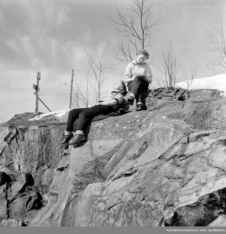 To jenter nyter vårsola på Frognerseteren stasjon. Holmenkollbanen. April 1958.