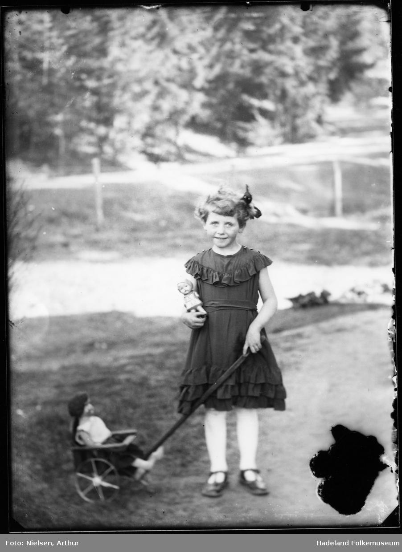 En lita jente med kjole og sløyfe i håret, står og holder ei lita lekevogn med ei dukke i.