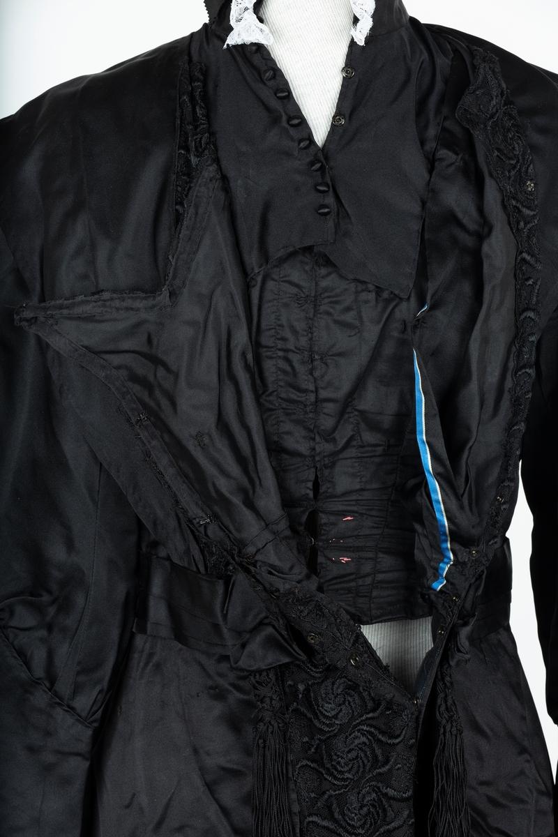 Kjole. Sort satinsilke. Trang fasongsydd overdel i merserisert bomullstoff, 3 bredder i rygg, skråstilt ryggsnitt mot ermer, 2 korte lengdesnitt på hvert forstykke, lukkes foran med 9 hekter. Tilbaketrukket skuldersøm. Livlinjen har innvendig strammebånd i lys silke. Dekksjal utenpå foret er festet kjolestoff gir kjolen det visuelle uttrykket. Front på overdel og skjørt pyntet med sort blonde. . Ståkragen har bølgende spile, og hvit blonde, antakelig nå ny. Isydd foret erme, posende ved lang mansjett, denne lukkes med 4 trykknapper. Sort blondestolpe midt foran. Skjørtet langt, skråklippet, slepende bak. Hekter, trykknapper og kuleknapper. Kantforing. Tilstand god Bruker: Inger Johanne Bjørnsatd f.  Næristortp i 1861 Giver: Inger Johanne Bjørnstad Olsen 1400 Ski, datterdatter av bruker