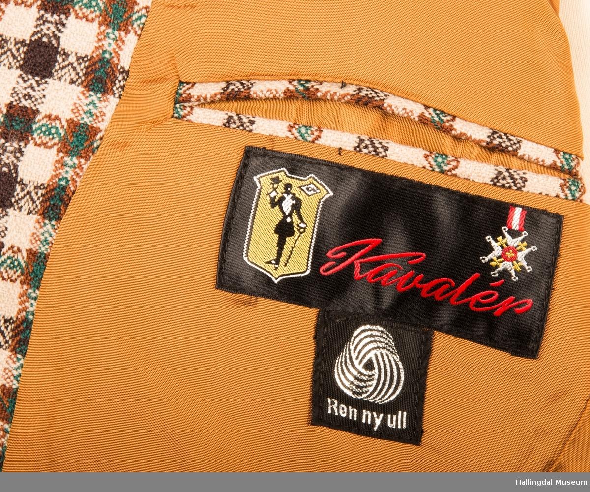 Kavaler dressjakke mønstrete ullstoff. Sennepsgult syntetisk silkefor. Jakka har skulderputer, store klaffer på lommene, 2 splitter bak.   Den er knept med 2 plastknapper midt framme.  1 pynteknapp på hvert erme.  Store slag.