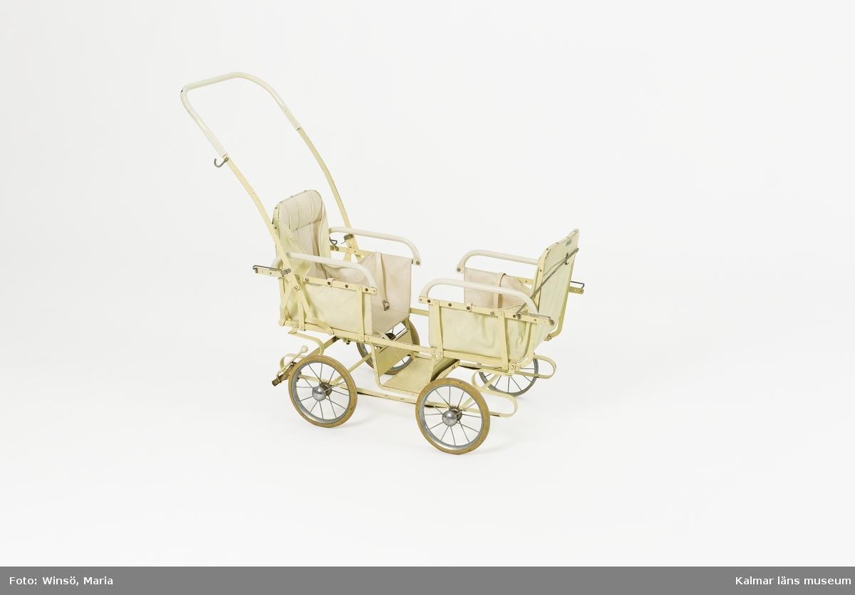 KLM 46366. Barnvagn, sittvagn. För två barn. Underrede av vitlackerad metall. Hjulen är av metall, gummiklädda med text: EMMALJUNGA TRELLEBORG. Två sitsar, vända mot varandra, av vit galon med midjebälte. I mitten ett fotstöd. På ryggstöden en metallskylt: Emmaljunga.