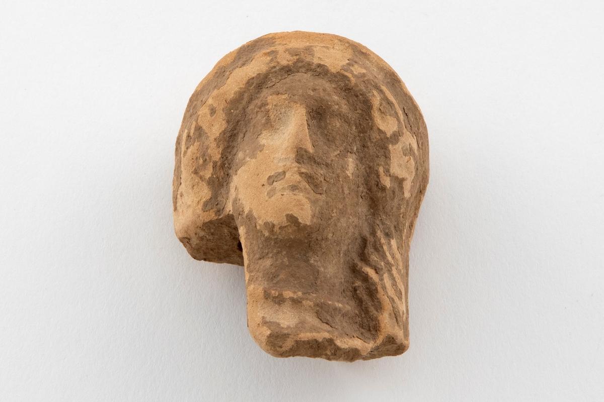 Fragment av figurin i terrakotta, bare hodet er bevart. Fremstiller en kvinne med oppsatt hår, frontalt fremstilt med hodeplagg. Lyst, rødlig gods, med grålige partier.