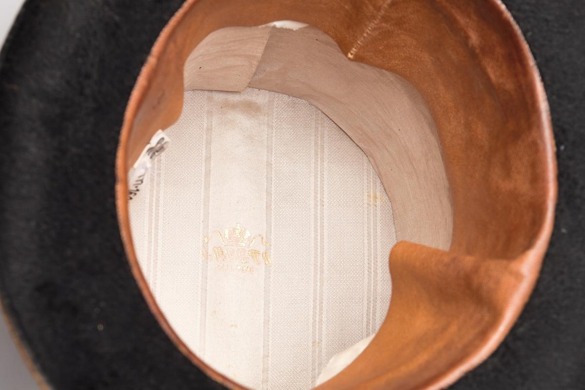Flosshatt (a) og hatteeske (b). Flosshatten er svart og har et pyntebånd med sløyfe. Innvendig er den foret med en bred lærkant og lyst stoff. Hatteesken er av papp, mørk brun og av samme fasong som hatten. Inne i hatten er et produsentstempel med en krone over navnet.