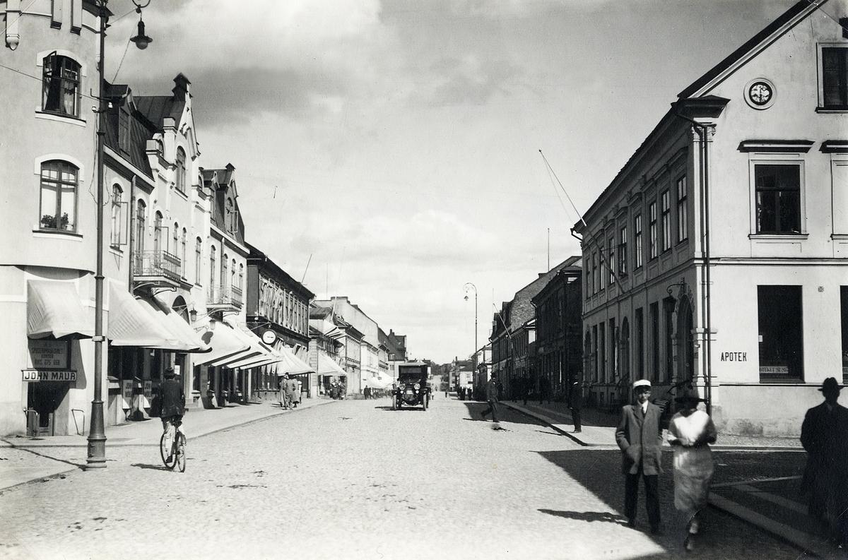 Storgatan, korsningen mot Bäckgatan, Växjö 1923. Till vänster ser man (närmast) familjen Feuks fastighet (kvarteret Klostret 8), med bl a Oscar Karlssons uraffär, följt av divera andra hus i kvarteren Klostret och Sunaman. Till höger ser man bl a apoteket Sigfrids lokaler i kvarteret Blenda (Blenda 1).   'Oscar Karlssons uraffär' - Oscar Carlsson (1885-1949), urmakare, kvarteret Uranus 3, Växjö.  (Källa: Bl a Folkräkning 1930, Växjö stadsfs, Riksarkivet. Sveriges Dödbok 1860-2017)