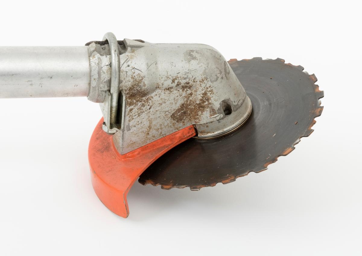 """Motorsag, rydningssag, ryddesag, av typen Husqvarna 165 RX beregnet for en person. Ryddesaga ser for registrator ut til å være tilnærmet komplett. Tanklokket mangler. Det er sprekkdannelser i godset til vinkelvekselen. For å holde vinkelvekselen fast til riggrøret, er det påmontert en metallklemme (eksosklemme).  Det følger ikke med bæresele til saga. I skogbruket brukes ryddesaga til ungskogpleie, tynning, rydding av kratt, mindre busker og trær.   Rydningssaga består av blad (sirkesagblad, sagklinge) og motor koblet til et langt stålrør/riggrør. Motor og blad er montert i hver sin ende av røret. Bladet er montert til en vinkelveksel/vinkelgir (gearhus). Kraftoverføringen fra motoren til sagbladet skjer ved hjelp av en aksel i det nevnte stålrøret/riggrøret. På riggrøret er det montert ei klamme med en ring til innfesting av bæresele. På venstre side av riggrøret er det påmontert et bånd, støttebånd, som ligger an mot brukerens kropp, høyre side. Saga styres ved et håndtak som på høyre side har påmontert gasspådrag og """"stoppknapp"""". Gass og stoppfunksjonen styres med en og samme hendel. Hendler for start og choke sitter på motorens/veivhusets høyre side side. Saga er utstyrt med sirkelsagblad for rydding av busker, mindre trær og kratt. Den kan også utstyres til å slå gress. Sagas bensinpåfylling er plassert på høyre side bak på motorhuset, ved siden av starthuset.  Rydningssaga startes ved hjelp av snortrekk/startsnor. Saga har totaktsmotor.   Ut fra bruksanvisning for Husqvarna 165 RX gjengis det her noen tekniske spesifikasjoner:  Sylindervolum: 65 kubikkcentimeter. Volum drivstofftank: 1 liter  Tenningssystem: Elekronisk Vekt: 10,8 kg tom tank, uten sele og transportbeskytter."""