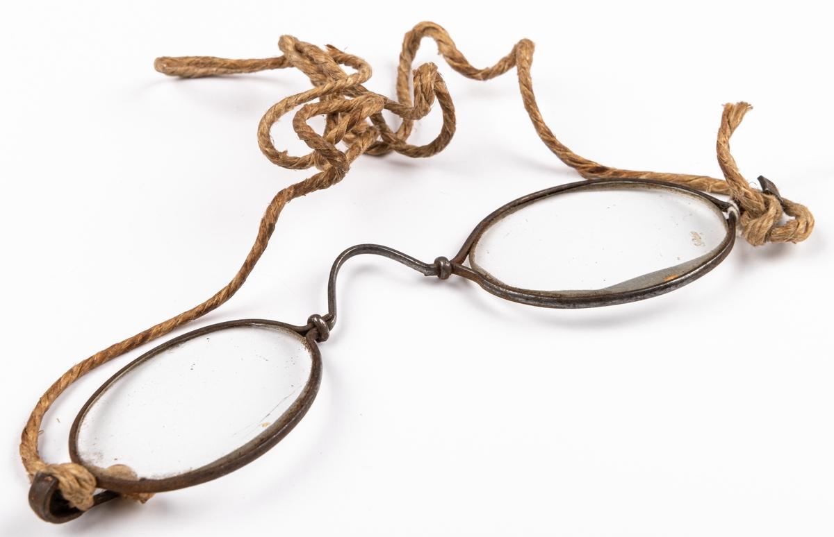 Glasögon, ovala med järnbågar, skalmar saknas. Fodral av papp med förgyllda metallkanter, brunt.
