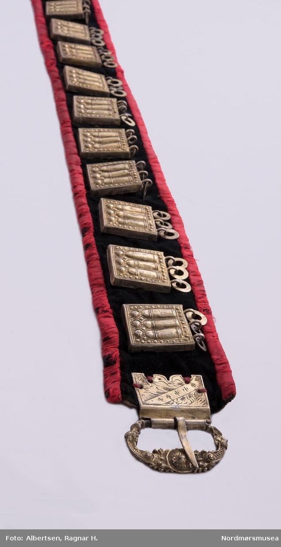 Belte i svart fløyel med lerretsfor og med rødt silkebånd påsydd rundt det hele. 15 sølvbrikker / støler med tre skiver (møllesteiner) i hver, er festet på. En rund gjennom-mønstret nål erstatter en støl. Spenne sydd på i tverrenden, den andre enden av beltet er avrundet med hull i stoffet etter feste. Spenna er sannsynligvis utført med samme overflate-teknikk som stølene og KM.1501, lueforgylling.