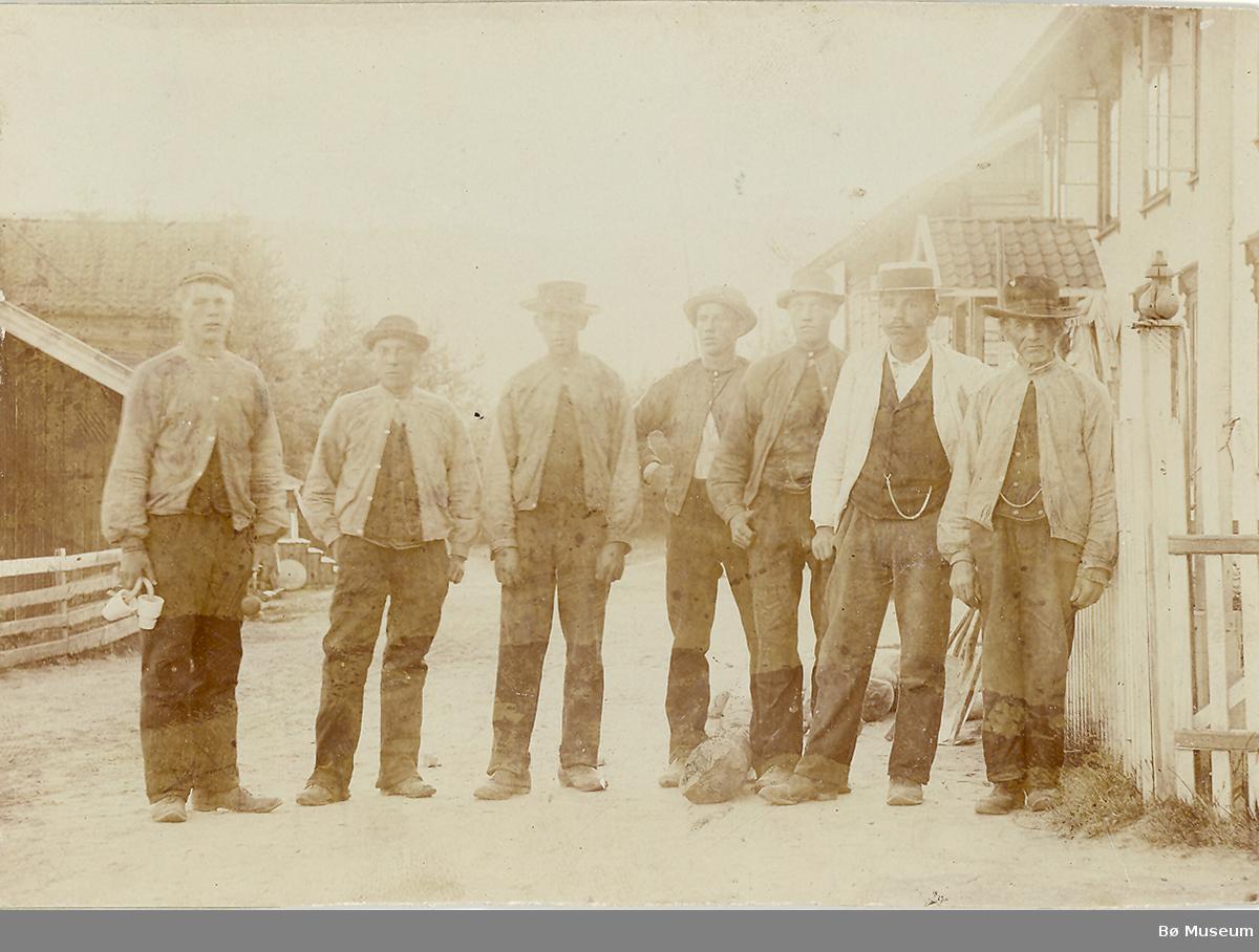 Sju menn fotografert i Gamlegata, Gvarv. Dei held truleg på med å sette opp stolpar til telefon? Dei er ukjente.