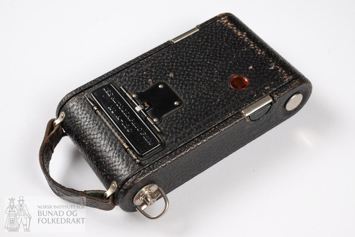 Fotoapparat med etui, No. 1 Autographic Kodak Junior. Kompakt belgkamera med utløser. Rød todelt skyveeske av kartong med svart stofftrekk og trykt gullfarget tekst.  Merke under linse: No.1 AUTOGRAPHIC KODAK JR. 13340. Merke rundt linse:  25 BT 50 KODAK BALL BEARING SHUTTER 14040 PATENTED IN U.S.A. JAN. 18, 1910 JAN. 7, 1913 1, 2, 3, 4