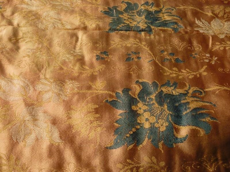 Duk? av mønstervevd silkestoff. Blomsterranker innvevd i grønt og kvitt på lyserød bunn. Kappe rundt av silke med litt skarpere rosafarge enn selve duken. Foret med grovt linlerret og gult mønstervevd silke.Rektangulert formet. Falmet og slitt i kappekantene.