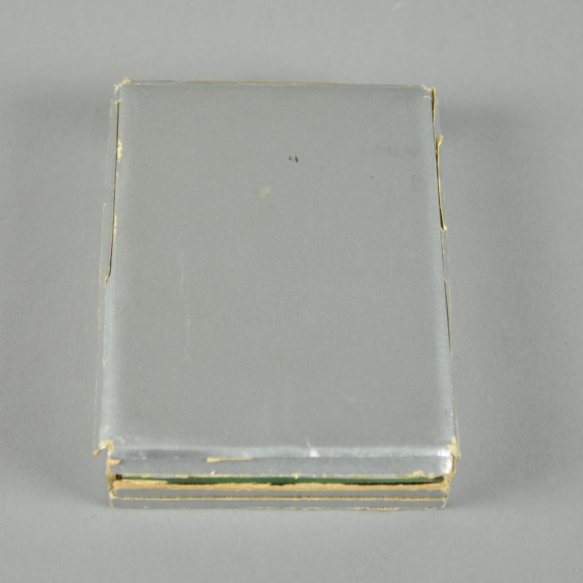 Etui til plakket fra 1940. Etuiet er av sølvfarget kartong med grønn fløyelspute. Rektangulær form.
