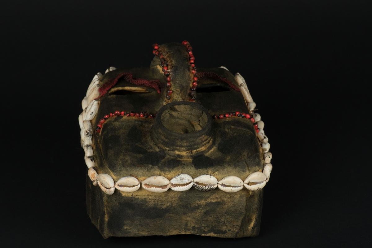 Rektangulär mask tillverkad av en dekorerad överdel av en plastdunk. Den avskurna dunken är klädd med textil, troligen ett nylontyg, som är delvis svartmålat. Två utskurna hål bildar ögonen på var sida om handaget som utgör näsan. Dunköppningen därunder blir en mun. Över ögonen sitter pålimmade vävda röda band i plast som ögonbryn.  Runt ansiktet sitter en rad med kaurissnäckor och runt handtaget/näsan samt på en rad mellan mun och näsa finns fastlimmade röda frön eller bönor. Snäckorna är fästade med tråd och på något ställe med metalltråd. Bönorna är trädda på ett snöre, sedan limmade.