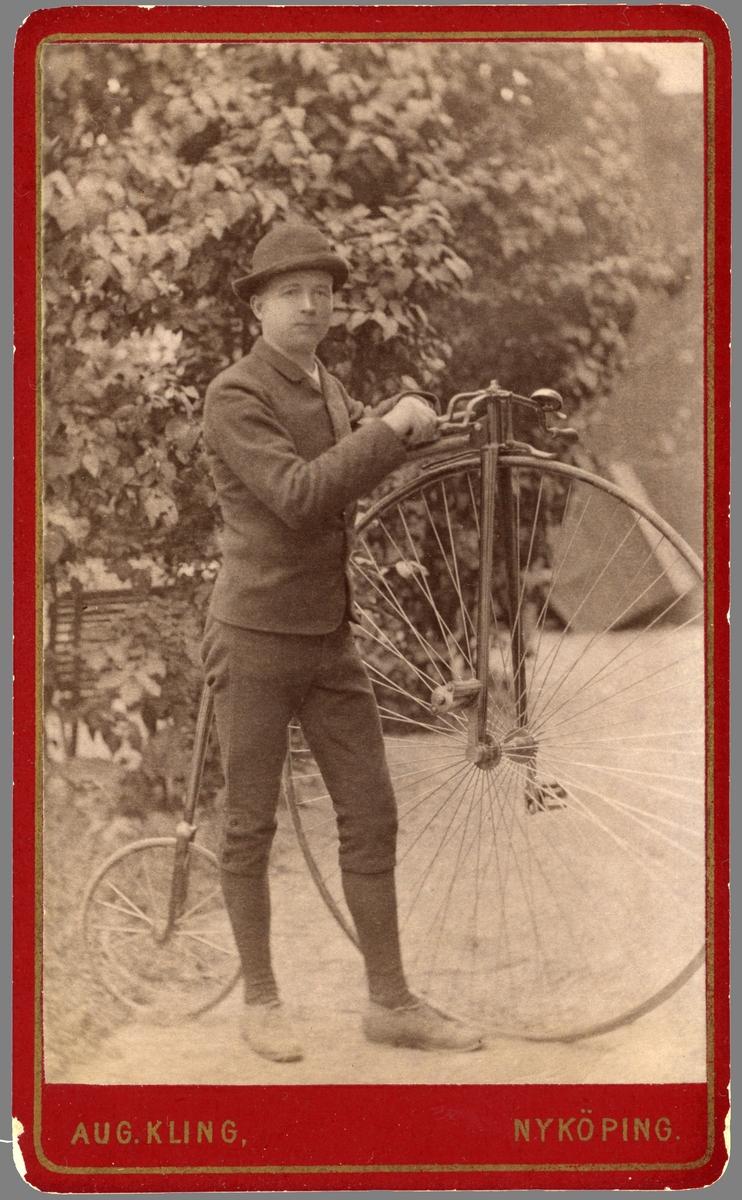 Porträtt av en stolt Hjalmar Ritzman invid sin järnhäst. Han var född i Linköping 1865 som son till muraren Anders Peter Ritzman och dennes hustru Anna Brita Andersdotter. I 20-årsåldern flyttade han med två äldre syskon till Nyköping. Hans liv tog honom vidare till Örebro som köpman.