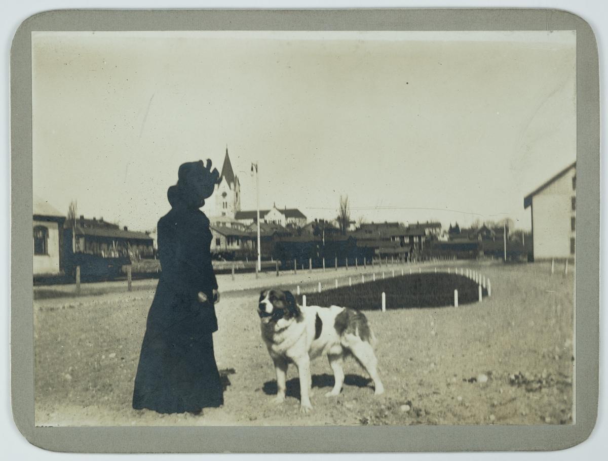 """En kvinna med en hund, """"Baron"""". Nora kyrka i bakgrunden.  Fotot taget i maj 1901."""