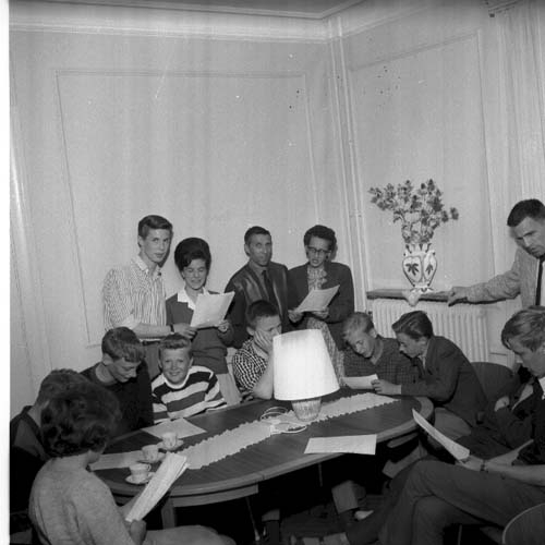 En samling med männiksor sitter runt ett bord och sjunger tillsammans. Alla har blivit tilldelade ett texthäfte.