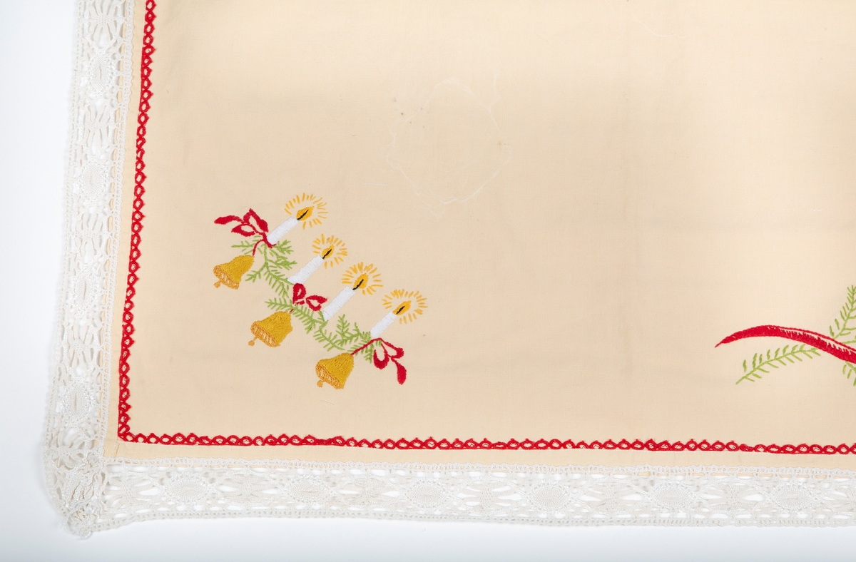 Juleduk. Kvadratisk.Brodert. Maskinkniplet (antakelig kant. Gråhvit bunn, rødt, grønt og gult mønster. 4 lys på granbar. 3 klokker Sydd og brukt av giver